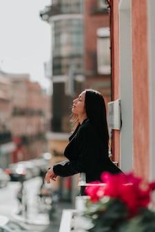 Mujer vestida de negro respirando en un balcón con flores rosas