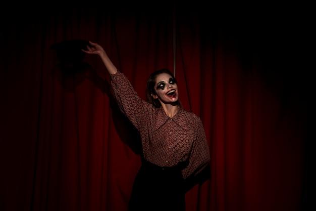 Mujer vestida de payaso saluda a la audiencia