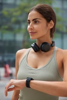 Mujer vestida con ropa deportiva comprueba los resultados del entrenamiento físico lleva auriculares inalámbricos alrededor del cuello plantea en borrosa