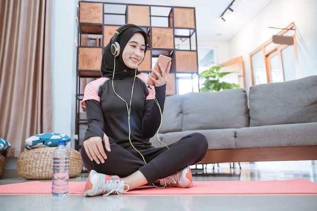 Una mujer vestida con ropa deportiva hijab con auriculares y un teléfono celular mientras escucha música se sienta en una alfombra con una pared de sofá