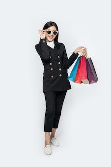 La mujer vestida con ropa oscura y anteojos, junto con muchos bolsos, para ir de compras
