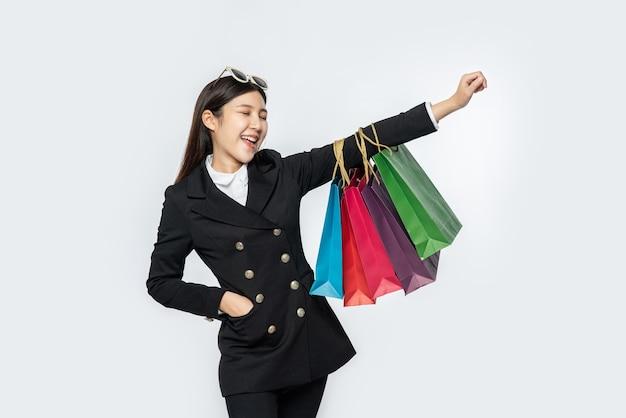 La mujer vestida con ropa oscura, junto con muchos bolsos, para ir de compras