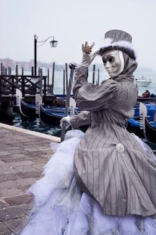 Mujer vestida con traje de carnaval veneciano hace gesto de saludo