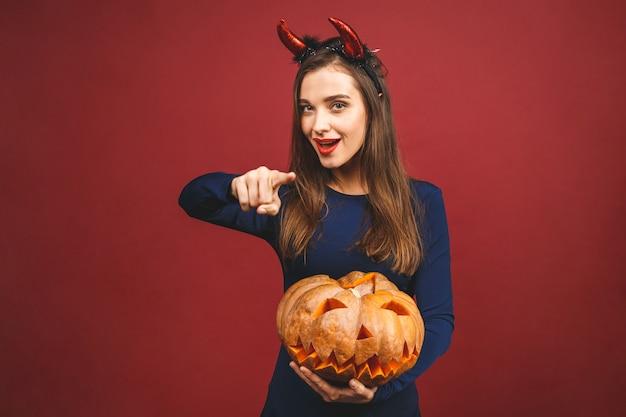 Mujer vestida con traje de diablo negro de halloween con diadema de bruja para una fiesta temática. ella sostiene la calabaza para un 'truco o trato'