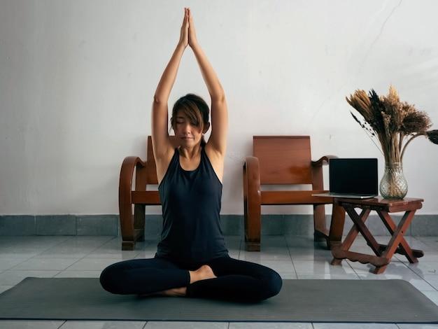 Mujer vestida con traje de ejercicio, sentada en la colchoneta, junta las manos y levanta la cabeza, cierra los ojos, medita antes de practicar yoga. en casa.