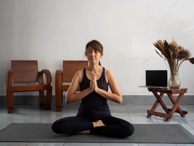 Mujer vestida con traje de ejercicio, sentada en la estera, junta las manos en el pecho y cierra los ojos, meditando antes del yoga. en casa, tiempo de relax