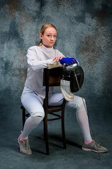 La mujer vestida con traje de esgrima con espada contra gris