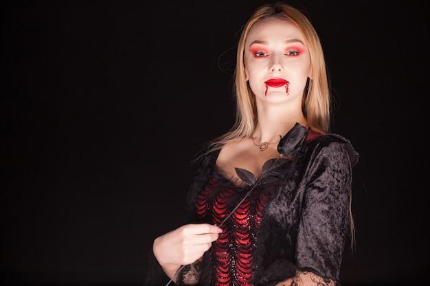 Mujer vestida con un traje de vampiro con una rosa sobre fondo negro.