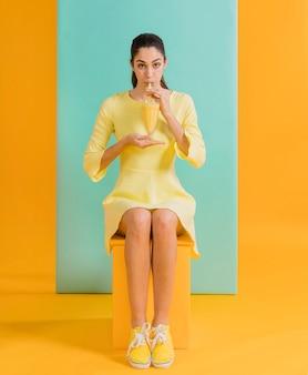 Mujer en vestido amarillo con jugo