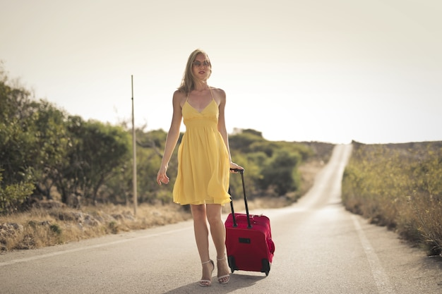 Mujer con un vestido amarillo y una maleta roja en la calle