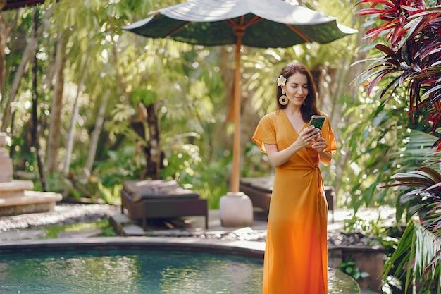Mujer en un vestido amarillo de pie junto a la piscina en un bali
