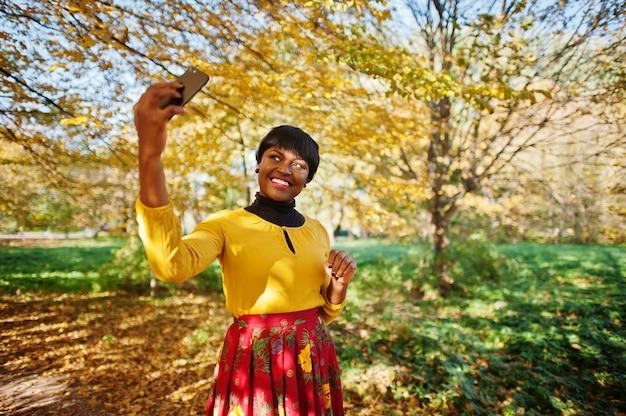 Mujer en vestido amarillo y rojo en el otoño dorado otoño park haciendo selfie en teléfono