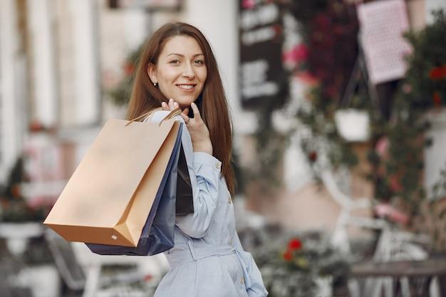 Mujer con un vestido azul con bolsa de compras en una ciudad