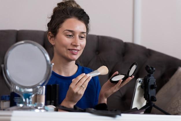 Mujer en vestido azul que presenta un vlog de maquillaje