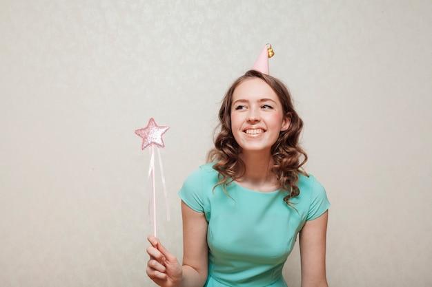 Mujer con vestido azul con un sombrero de fiesta y mirando a otro lado
