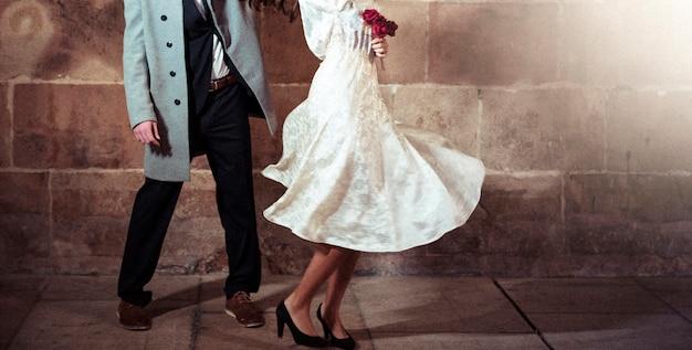 Mujer en vestido bailando con hombre en calle