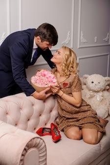 Mujer en el vestido beige sentada en el sofá recibe un ramo de flores a su hombre