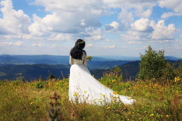 Una mujer con un vestido blanco camina en las montañas.