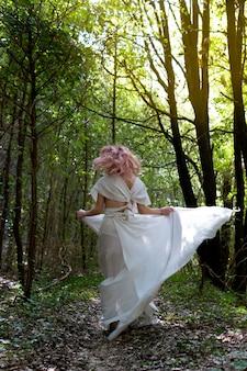 Una mujer con un vestido blanco en medio del bosque.