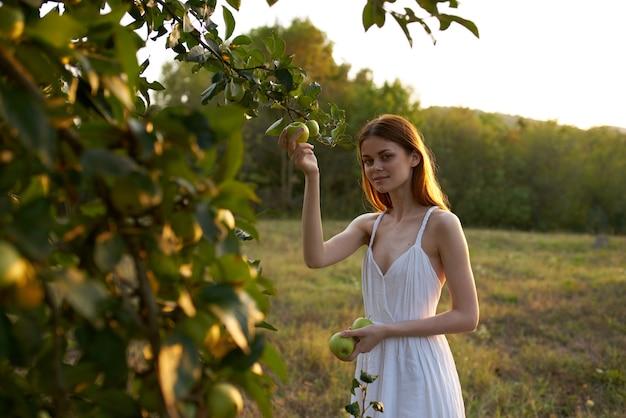 Mujer en vestido blanco en la naturaleza cerca de frutos de manzano