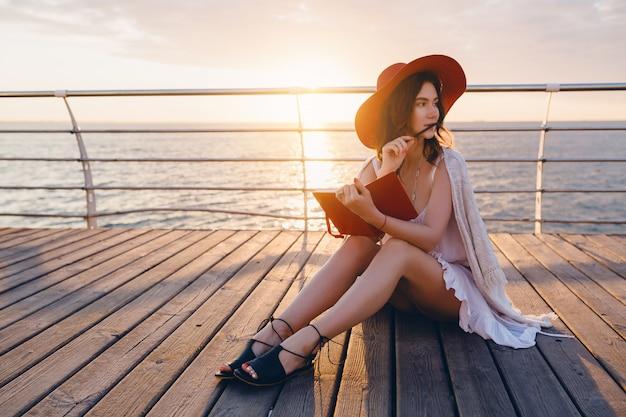 Mujer con vestido blanco sentada junto al mar al amanecer pensando y tomando notas en el libro diario en un estado de ánimo romántico con sombrero rojo