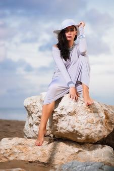 Mujer con vestido blanco sentado en una roca en la playa y con sombrero blanco.