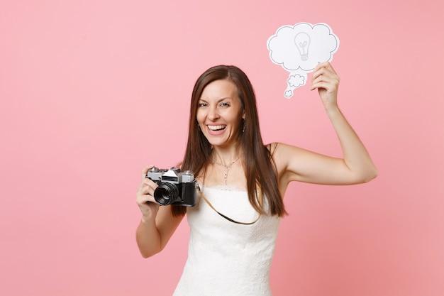 Mujer con vestido blanco sostenga cámara de fotos vintage retro, diga bocadillo de diálogo de nube con bombilla eligiendo fotógrafo