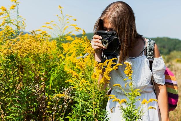Mujer con vestido blanco tomando fotos de flores amarillas