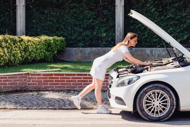 Una mujer con un vestido blanco está tratando de reparar su auto blanco por su cuenta que se descompuso en el costado del ...