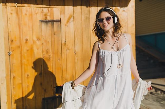 Mujer en vestido blanco de verano escuchando música con auriculares bailando y divirtiéndose