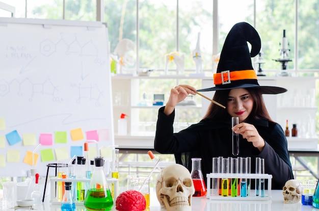 Mujer con vestido de bruja y probeta en laboratorio