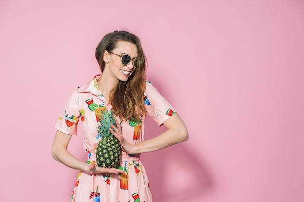 Mujer en vestido colorido con una piña