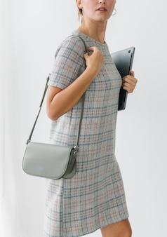 Mujer en un vestido a cuadros gris sosteniendo una computadora portátil