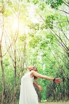 Mujer con vestido estirando los brazos en el bosque