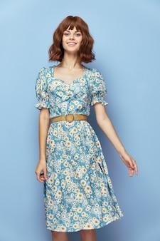 Mujer en vestido de flores sonríe vistiendo ropa de verano