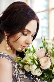 Mujer en vestido y un gran ramo de flores.