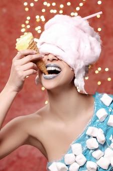 Mujer en vestido inusual hecho de malvavisco y peluca de algodón de azúcar
