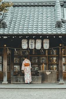 Mujer con vestido kimono naranja y blanco de pie cerca de la casa