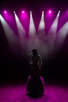 Mujer en vestido largo actuando en el escenario. mujer cantando en el escenario frente a las luces.