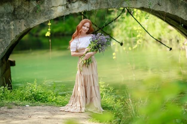Una mujer con un vestido largo camina cerca del bosque viejo puente sobre el río