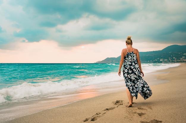 Mujer en vestido largo caminando por la orilla del mar