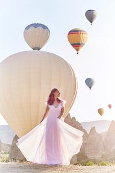 Mujer con un vestido largo y globos aerostáticos