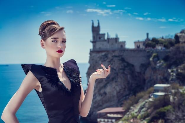 Mujer con un vestido largo negro sobre un fondo de un antiguo castillo.
