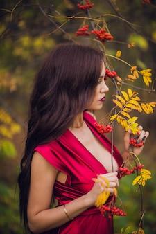 Mujer en un vestido largo rojo solo en el bosque. fabulosa y misteriosa imagen de una niña en un bosque oscuro en el sol de la tarde. sunset, princess se perdió.