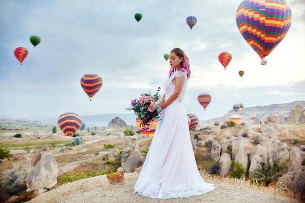 Mujer en un vestido largo sobre fondo de globos aerostáticos