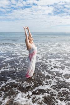 Mujer con un vestido en el mar disfrutando de su libertad con los brazos arriba