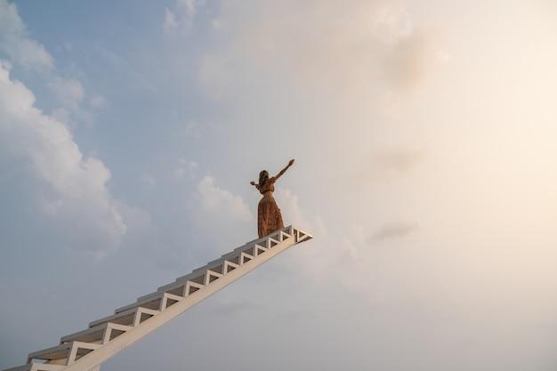 Mujer con vestido marrón, levantando las manos subiendo por la escalera. la libertad se siente bien.