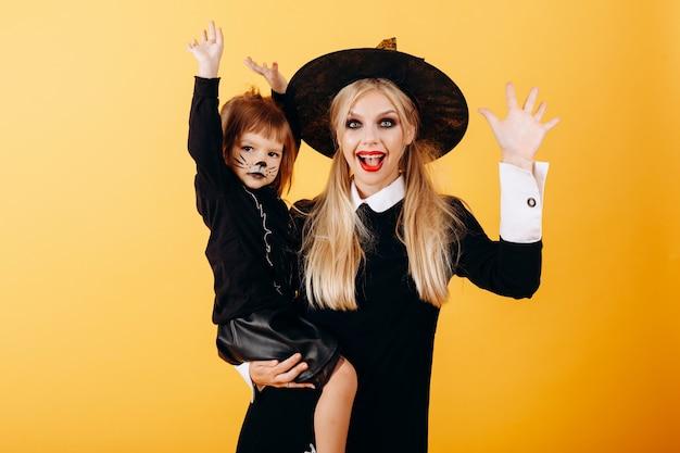 Mujer en vestido de mascarada y sombrero posando sosteniendo a la niña y mirando a la cámara divertida