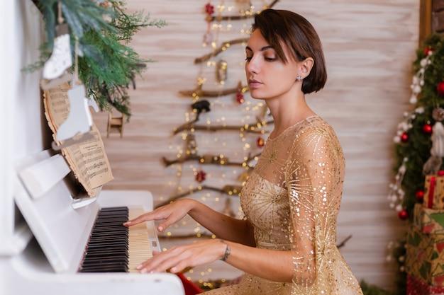 Mujer con vestido de navidad dorado brillante de noche tocando el piano en casa. Foto gratis