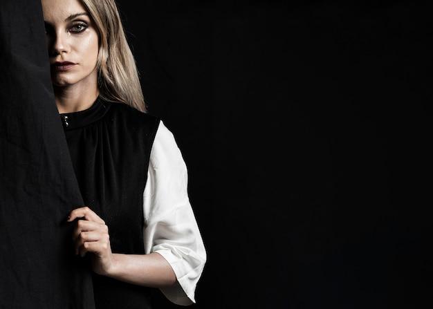 Mujer con vestido negro y copia espacio